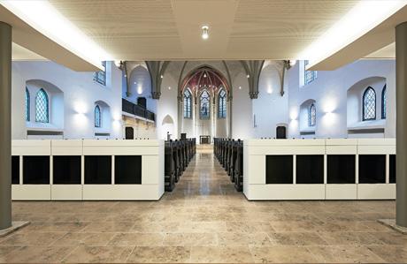 Blick in Richtung Altar vom Haupteingang. Wegbegleitende Lichtvouten an der Decke der Orgelempore.