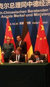 v.l. Bundeskanzlerin Angela Merkel, Chinas Ministerpräsident Li Keqiang, Architekt Axel Koschany und Yang Weidong, CEO der China Design Group, bei der Unterzeichnung des Deutsch-Chinesischen Kooperationsabkommens im chinesischen Hefei am 30.10.2015 Foto: Koschany + Zimmer Architekten KZA
