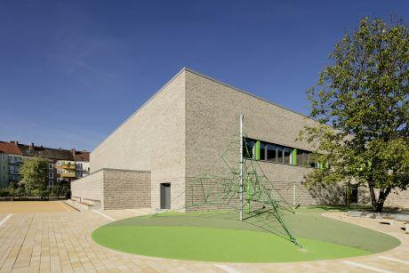 Sporthalle außen: Großzügige Freiflächen bieten Platz zum Toben und vermitteln durch ihre interne Lage gleichzeitig Geborgenheit und Sicherheit.